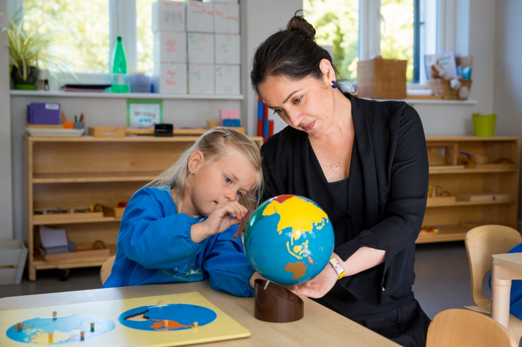 Teacher and child looking at globe