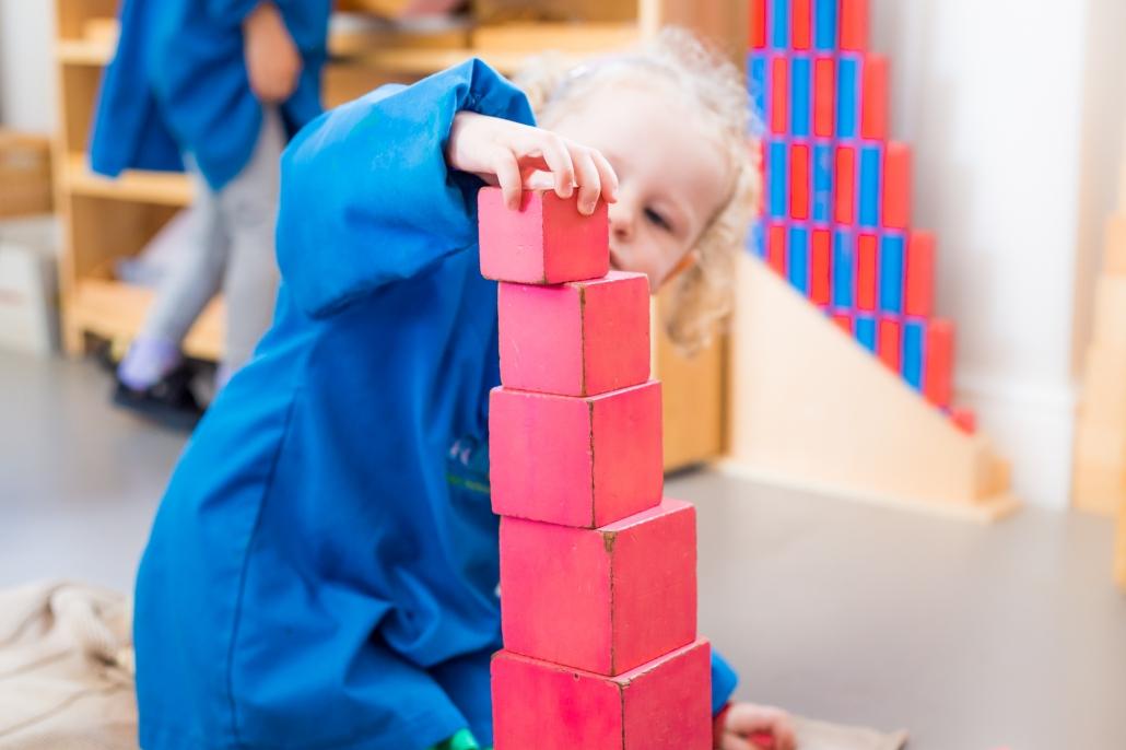 girl building Montessori tower
